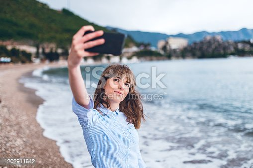 Young beautiful caucasian woman taking selfie at the beach.