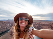 View of a woman taking selfie picture at the famous horseshoe bend by the Colorado river at sunset, beautiful dramatic colourful sky. people travel concept