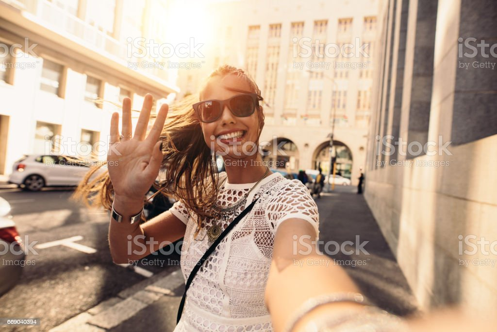 Young woman taking selfie in a street surrounded by buildings. stock photo