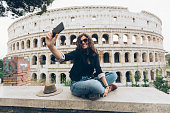 Young woman taking selfie on street in Italy, in front of Coliseum.