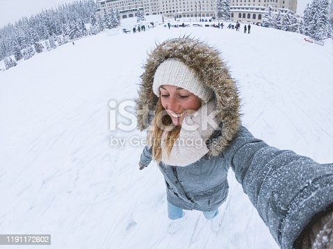 Young woman taking selfie on frozen lake with ice skates on shoulders; having fun in winter vacations