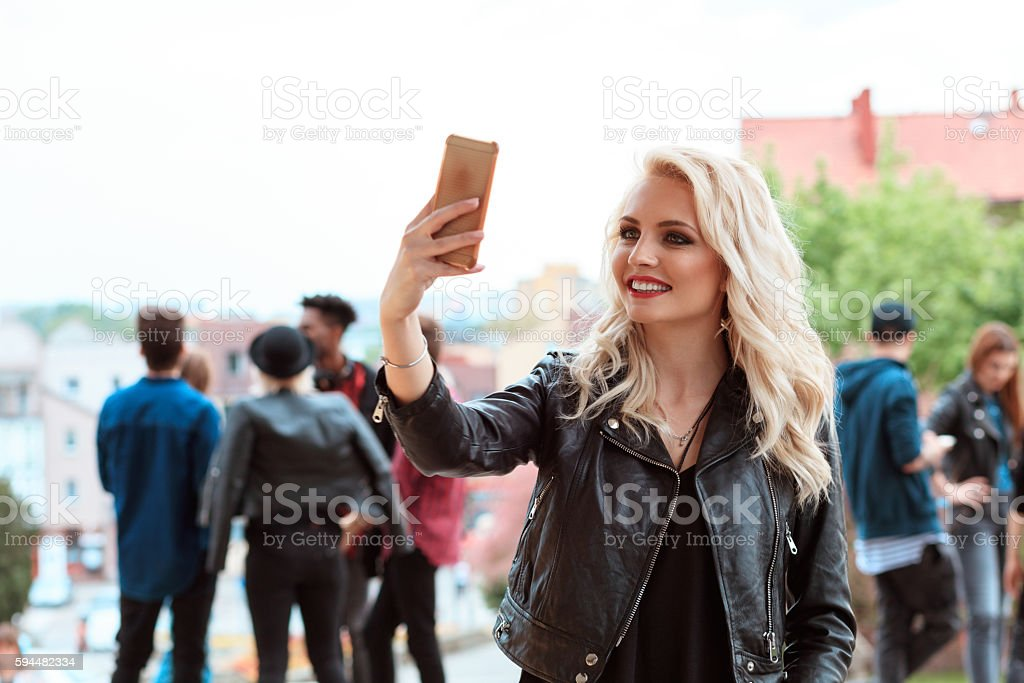 Young woman taking selfie outdoor Young beautiful blonde woman taking selfie outdoor, using smart phone. Multi ethnic group of people in the background. 20-29 Years Stock Photo