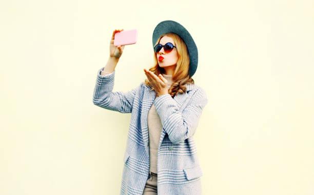 Junge Frau, die die Selfie Bild durch Einblasen von Smartphone rote Lippen senden süße Luft Kuss in rosa Mantel Jacke, runden Hut, auf Wand Hintergrund auf Stadtstraße – Foto