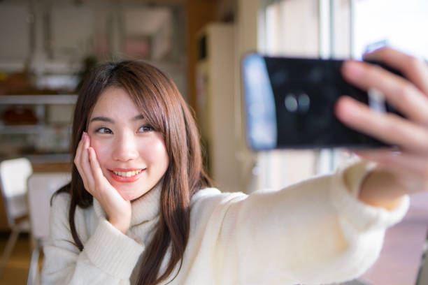 young woman taking selfie picture in cafe - self portrait photography stock pictures, royalty-free photos & images