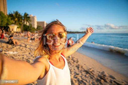 Young woman taking selfie picture on beautiful beach in Honolulu, Hawaii, USA