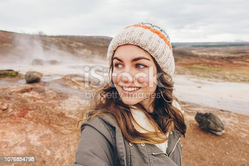 Young happy woman traveler taking selfie portrait in Icelandic landscape