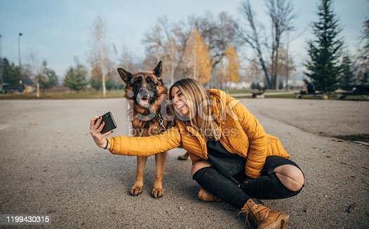 636418612 istock photo Young woman taking selfie with dog in the park 1199430315