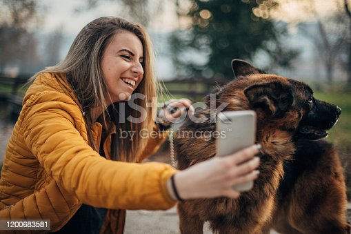 636418612 istock photo Young woman taking selfie with dog in the park 1200683581