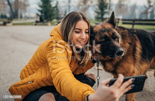 636418612 istock photo Young woman taking selfie with dog in the park 1201640569