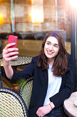 istock Young woman taking selfie with smart phone in cafe Paris 539246876