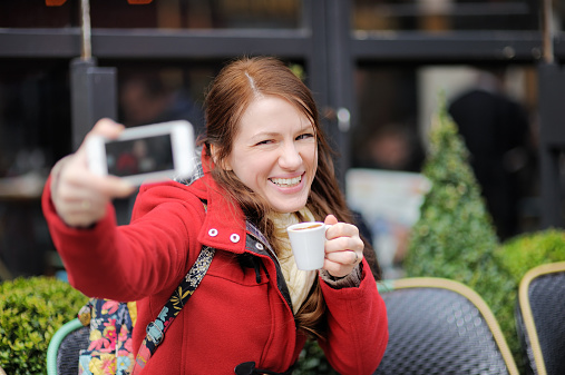 Young woman taking selfie with smart phone in street cafe