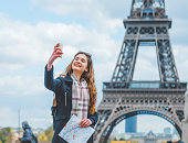Young beautiful girl take a selife pic with smart phone in Paris, France.