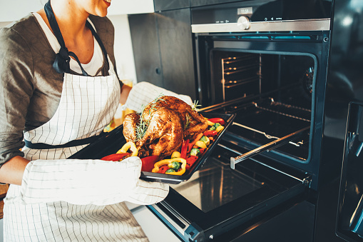 Young woman taking the turkey out of the oven,