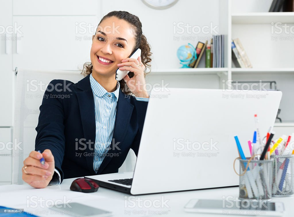 young woman talking by mobile in office stock photo