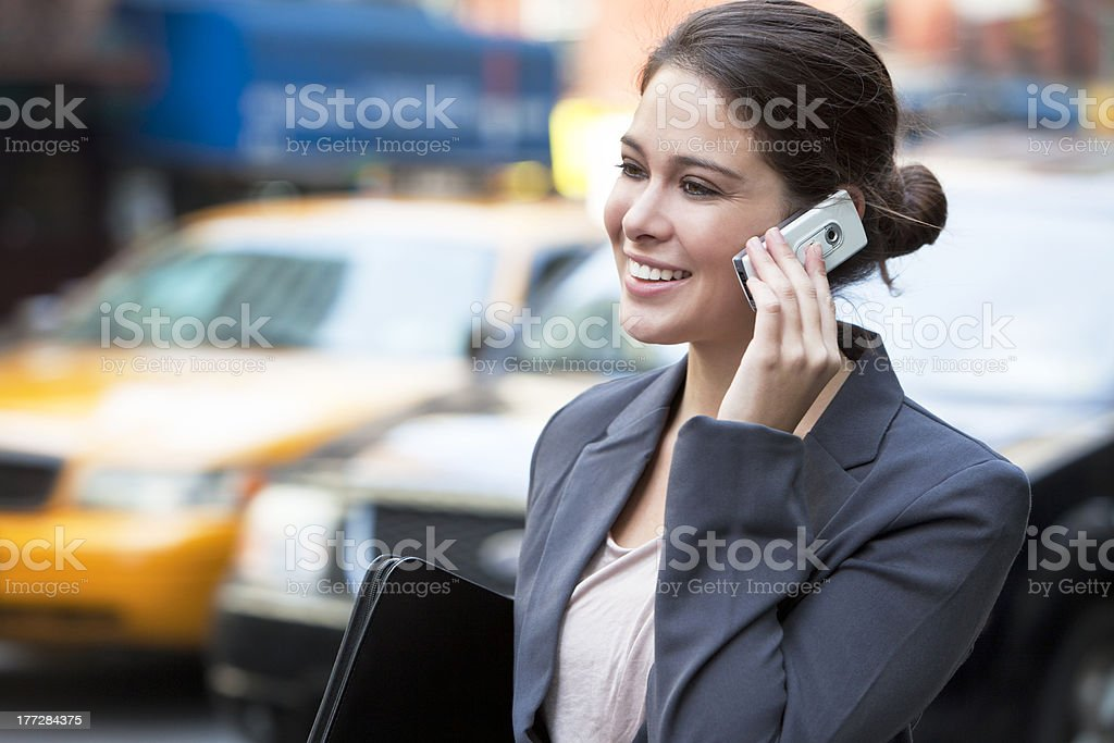 Young Woman Talking on Cell Phone by Yellow Taxi royalty-free stock photo