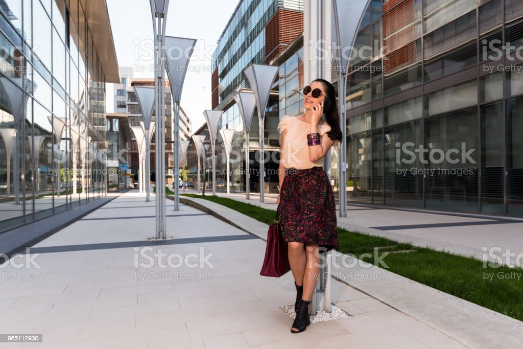 Young woman talking on mobile phone in front of an office building zbiór zdjęć royalty-free