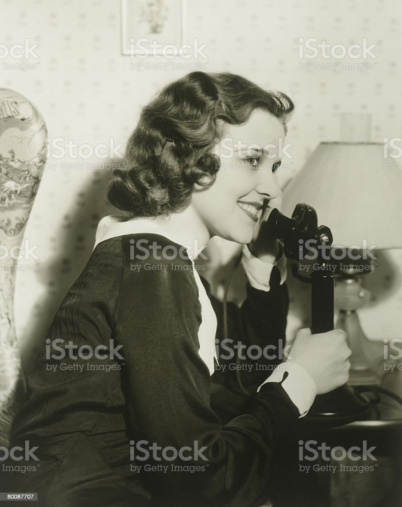 Young woman talking on phone in living room 免版稅 stock photo