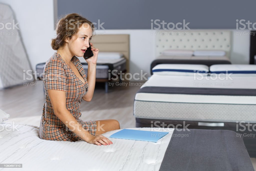 Young woman sitting on bed in mattress store and talking on phone