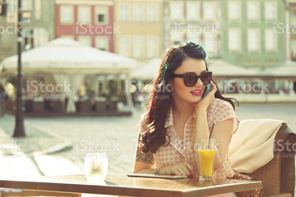 Young woman talking on phone in the outdoor restaurant Young hipster woman with tatoo on her arm wearing sunglasses sitting at the table in the outdoor restaurant in the city and talking on phone. Orange juice on the table. Summer time.  20-24 Years Stock Photo