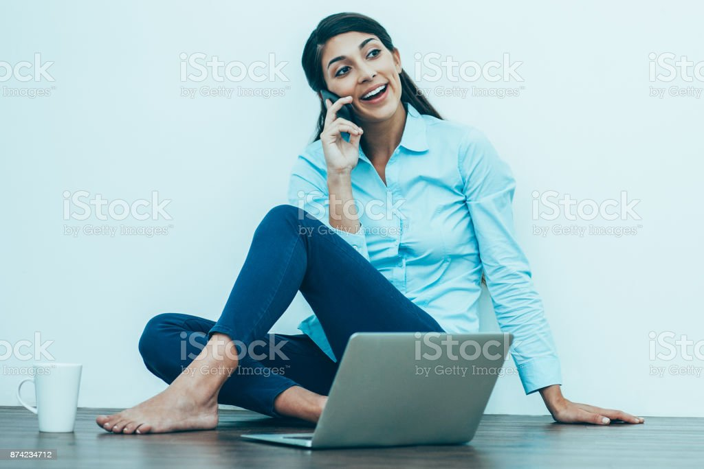 Young Woman Talking on Phone on Floor with Laptop стоковое фото