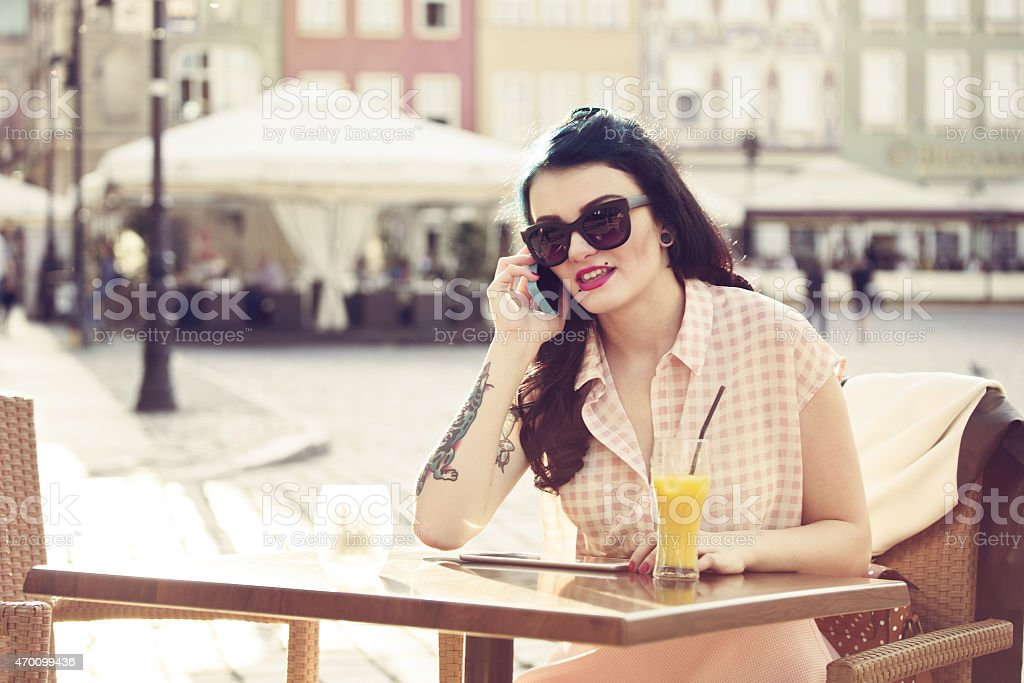 Young woman talking on phone outdoor Young hipster woman with tatoo on her arm wearing sunglasses sitting at the table in outdoor restaurant in the city and talking on phone. Orange juice on the table. Summer time.  2015 Stock Photo