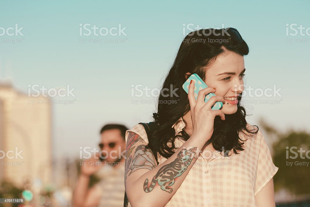 Young woman talking on phone outdoor Smiling young woman with tatoo on her arm talking on phone outdoor. Blured man on phone in the background. Summer time.  2015 Stock Photo