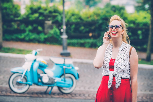 young woman talking on phone with her old-fashioned motorcycle in background - giovani motorino italia parlano foto e immagini stock