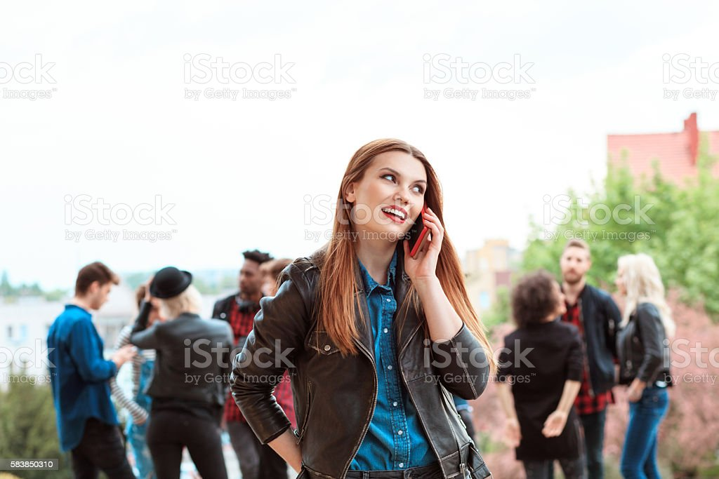 Young woman talking on smart phone outdoor Young beautiful woman talking on smart phone outdoor. Multi ethnic group of people int he background. 20-29 Years Stock Photo