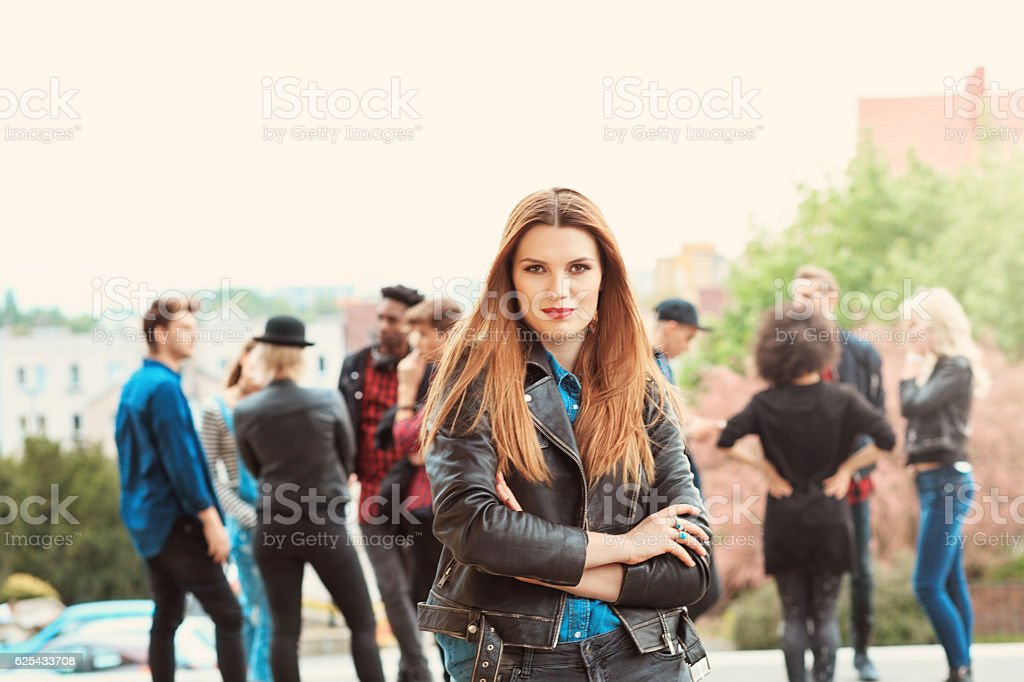 Young woman talking on smart phone outdoor Outdoor portrait of beautiful young woman looking at camera. Multi ethnic group of people int he background. 20-29 Years Stock Photo