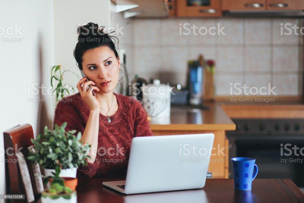 Jeune femme parlant sur le téléphone portable à la maison photo libre de droits