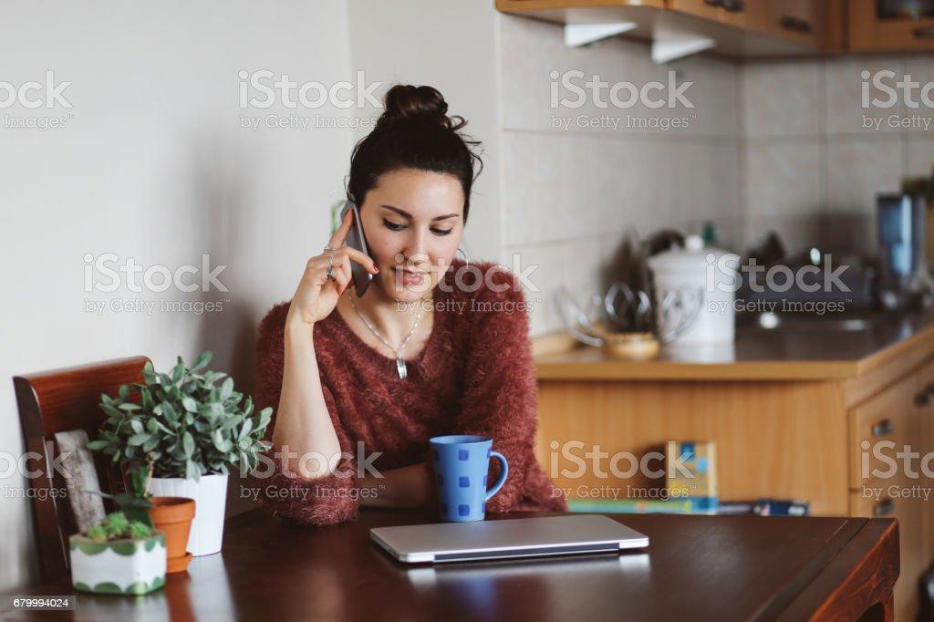 Junge Frau im Gespräch auf dem Handy zu Hause – Foto