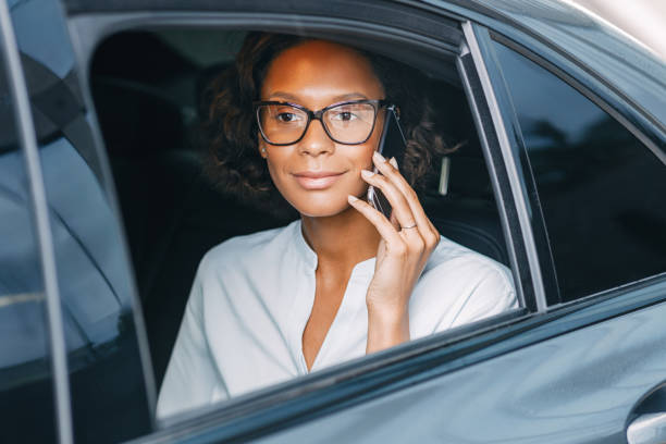 Young woman talking on the cellphone while sitting on back seat of a taxi stock photo