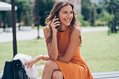 Beautiful young woman sitting outdoors in the park and talking on the phone