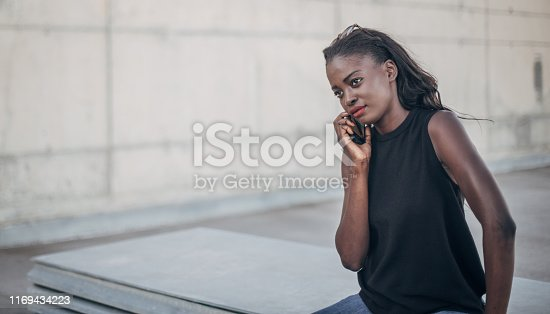 Young black woman talking on the phone outdoors