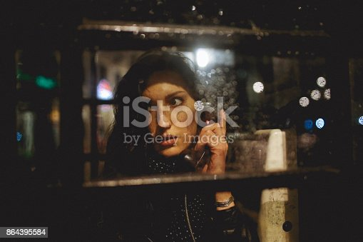Young woman talking on the public payphone in London at night.