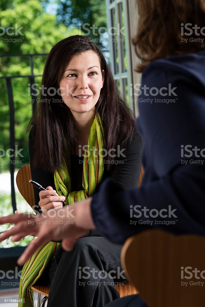 Young Woman Talking To a Colleague. stock photo