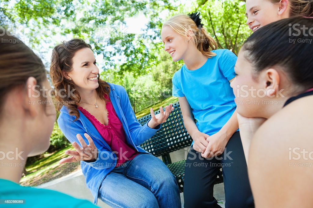 Young woman talking to group of teenage girls royalty-free stock photo