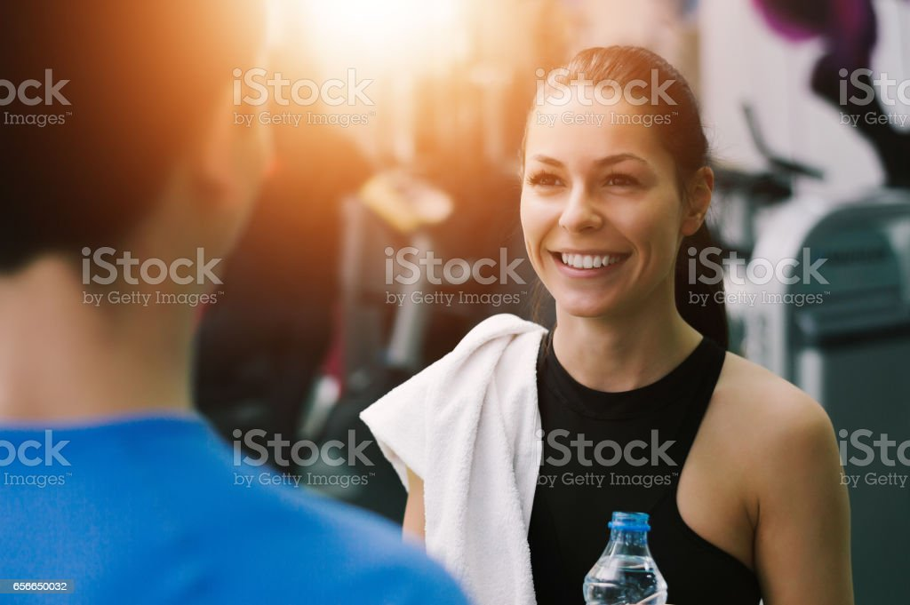 Young woman talking to her fitness trainer in the gym smiling stock photo