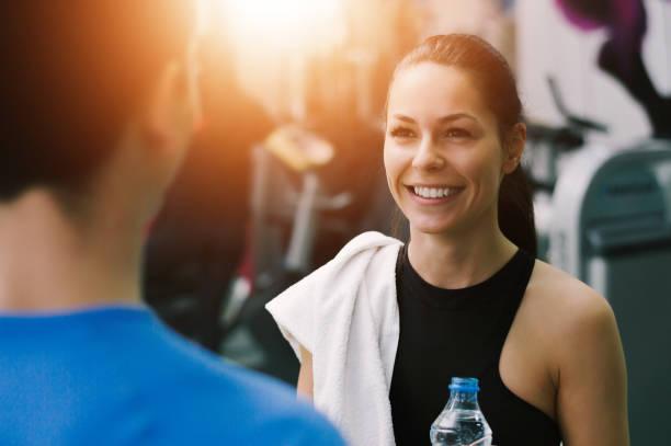 mujer joven hablando con su entrenador de fitness en el gimnasio sonriente - entrenador personal fotografías e imágenes de stock