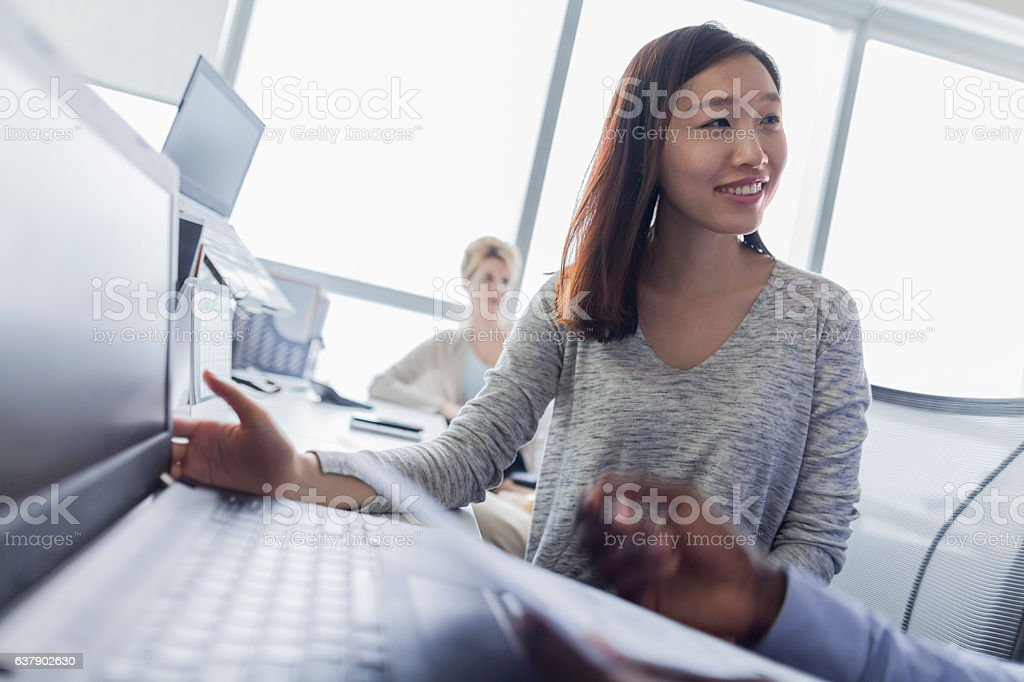 Young woman talking with colleague in technology department stock photo