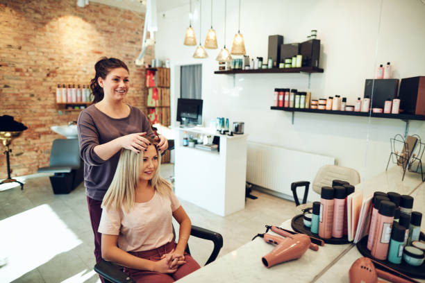 young woman talking with her hairstylist during a salon appointment - small business stock pictures, royalty-free photos & images