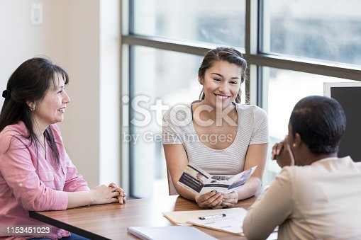 Young woman and her mother talk with a female bank employee about a student loan.
