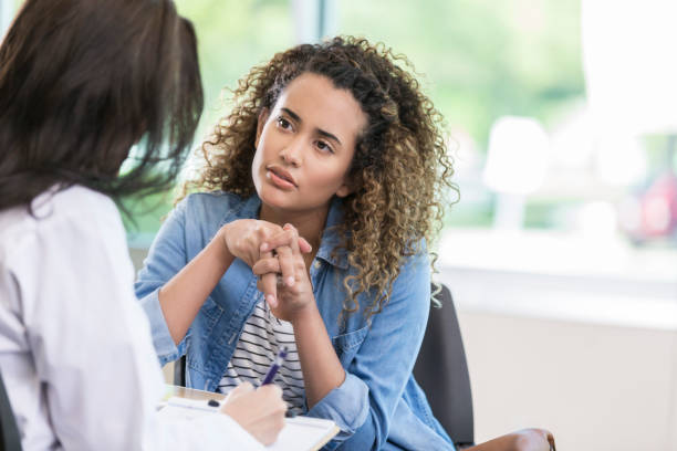 Young woman talks with doctor stock photo