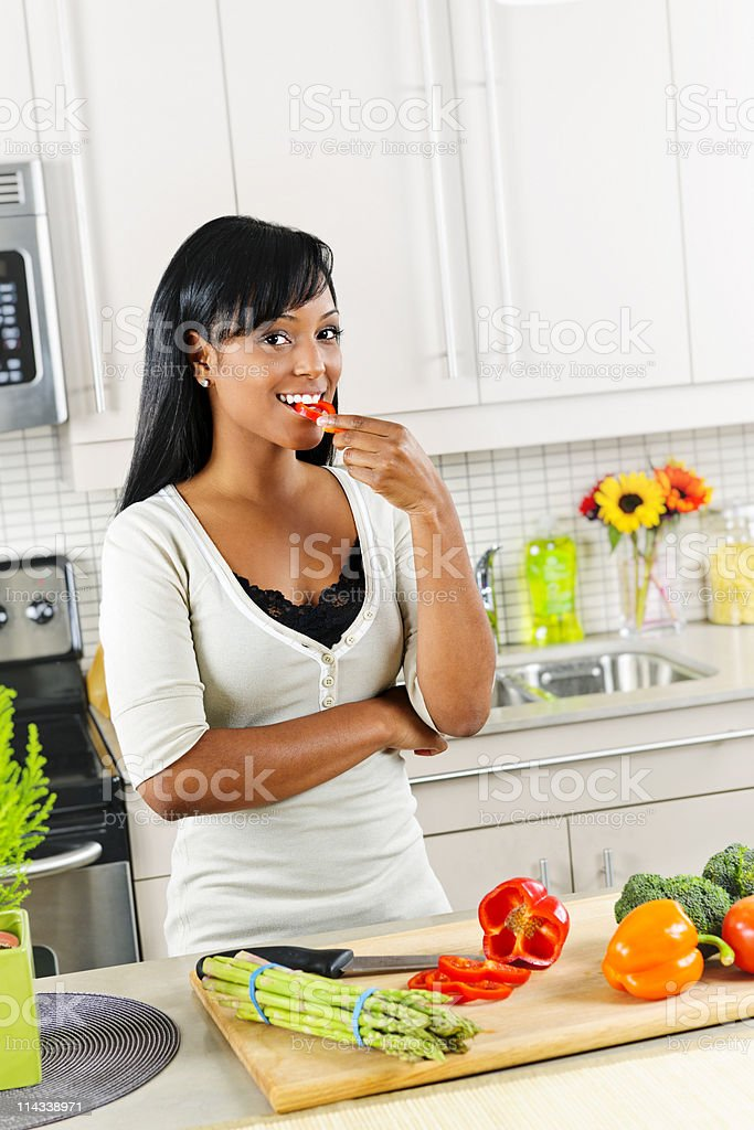 Young woman tasting vegetables in kitchen stock photo