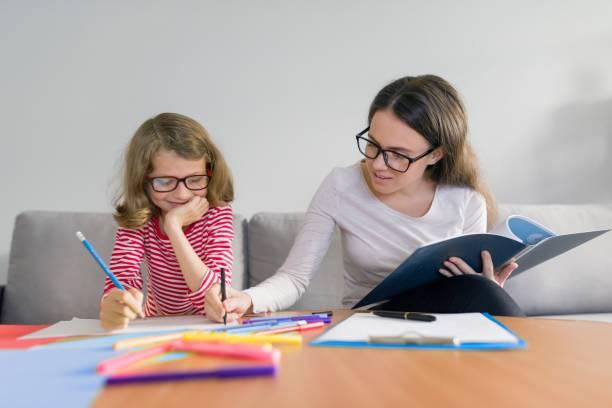 Genç kadın öğretmen ilkokulda kız öğretir stok fotoğrafı