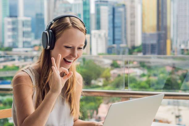 die junge frau unterrichtet eine fremdsprache oder lernt eine fremdsprache im internet auf ihrem balkon vor dem hintergrund einer großstadt. online-sprachschule lebensstil - england stock-fotos und bilder