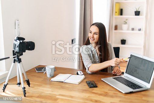Online teacher, mentor. Young woman teaches and records video lessons, the camera on a tripod in front of the girl