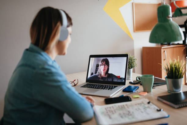 Young woman teleconferencing with sister on laptop on conference call Woman teleconferencing with sister on laptop due to COVID-19 lockdown zoom stock pictures, royalty-free photos & images