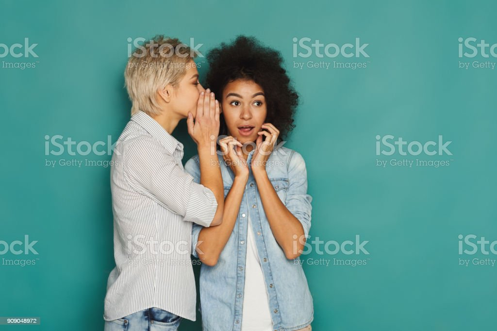 Young woman telling her friend some secrets royalty-free stock photo