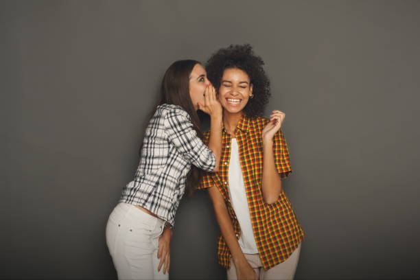 Young woman telling her friend some secrets stock photo